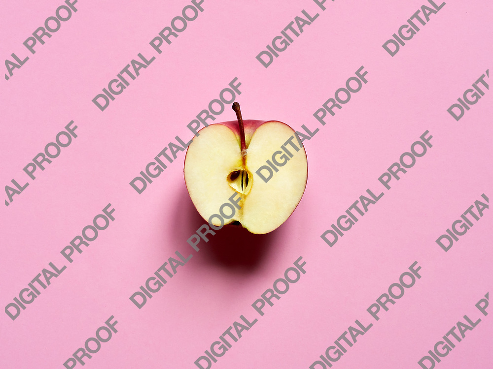 Red apple sliced by half isolated in studio over a pink background viewed from above