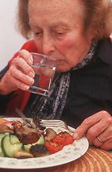 Elderly woman drinking glass of water,
