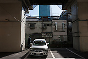 A car parked in a parking lot under the supports of an expressway overpass in Hiroo, Tokyo, Japan. Friday February 3rd 2012
