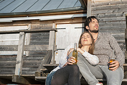 Man woman relaxing sunbathing jetty drinking beer