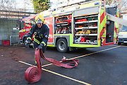 London Fire Brigade, station training session. A Fire fighter gets the hoses off the fire engine. Throwing it to unravel it.