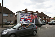 A Lorry drives through the constituency of Barking and Dagenham with a poster of British National Party Leader Nick Griffin on the back as young men drive past in a car.