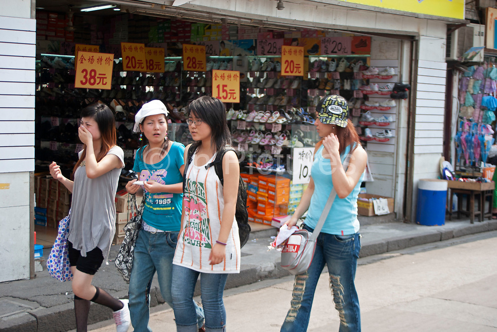 Young women taking on western fashion in Shanghai, China.