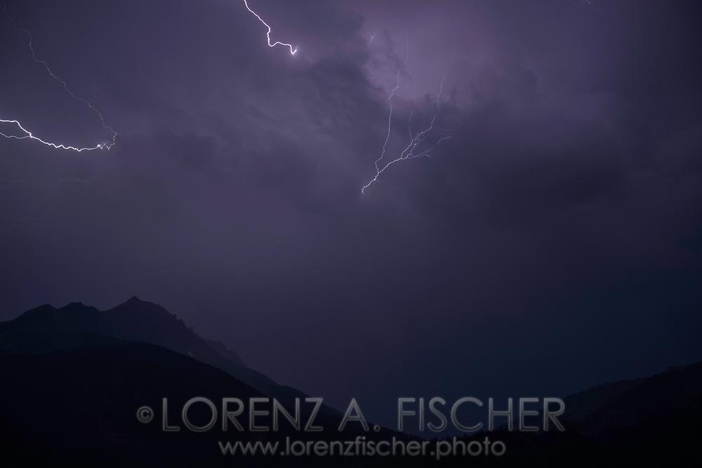 A lightning storm over the Piz Arblatsch in the Oberhalbsteiner Alps viewed from Savognin at dusk, Parc Ela, Grisons, Switzerland