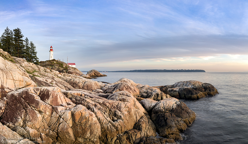 The rocky shore and the Point Atkinson Lighthouse at Lighthouse Park in West Vancouver, British Columbia, Canada.   Photographed from West Beach. English Bay/Burrard Inlet and Point Grey, and UBC (Vancouver) are in the background. The Point Atkinson Lighthouse was constructed in 1912 and is a National Historic Site in Canada.