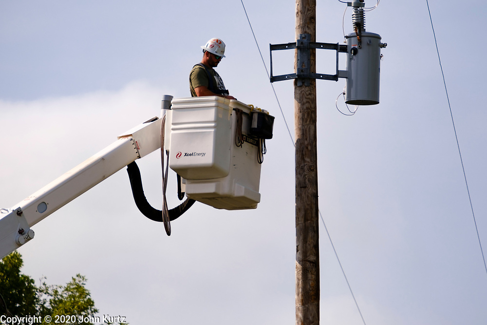 """12 AUGUST 2020 - SLATER, IOWA: A crew from XCel Energy, a Minnesota utility, repair power lines in Slater Wednesday. Power to the town was knocked out in the storm Monday. More than 145,000 Iowans are without power more than 48 hours after the storm. According to Iowa Governor Kim Reynolds, the storm damaged 10 million acres of corn and soybeans in Iowa, about 1 one-third of Iowa's 32 million acres of agricultural land. Justin Glisan, Iowa's state meteorologist, said the storm Monday, Aug. 10, lasted 14 hours and traveled 770 miles through the Midwest before losing strength in Ohio. The storm was a seldom seen """"derecho"""" that packed straight line winds of nearly 100MPH. The storm pummelled Midwestern states from Nebraska to Ohio.    PHOTO BY JACK KURTZ"""