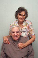 Elderly couple with wife standing behind husband with arms around his shoulders,