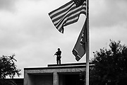 """10282017 - Shelbyville, Tennessee, USA: A police officer stands on a building with a rifle as neo-nazi and white nationalist group members walk to their vehicles after the """"White Lives Matter"""" rally in downtown Shelbyville, Tennessee. The rally, and the counter rally were the largest such gatherings since the deadly Charlottesville Unite the Right rally in August."""