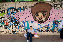 stock photo of a girl siting on a wall with graffti in russia