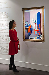 """© Licensed to London News Pictures. 18/11/2016. London, UK. A staff member views """"Interior, The Red Chair"""" by Francis Campbell Boileau Cadell (est. GBP250-350k), at the preview at Sotheby's of works on view at four upcoming November auctions featuring Modern & Post-War British Art, A Painter's Paradise (Julian Trevelyan & Mary Fedden at Durham Wharf), Scottish Art and Picasso Ceramics from the Lord & Lady Attenborough Private Collection. Photo credit : Stephen Chung/LNP"""