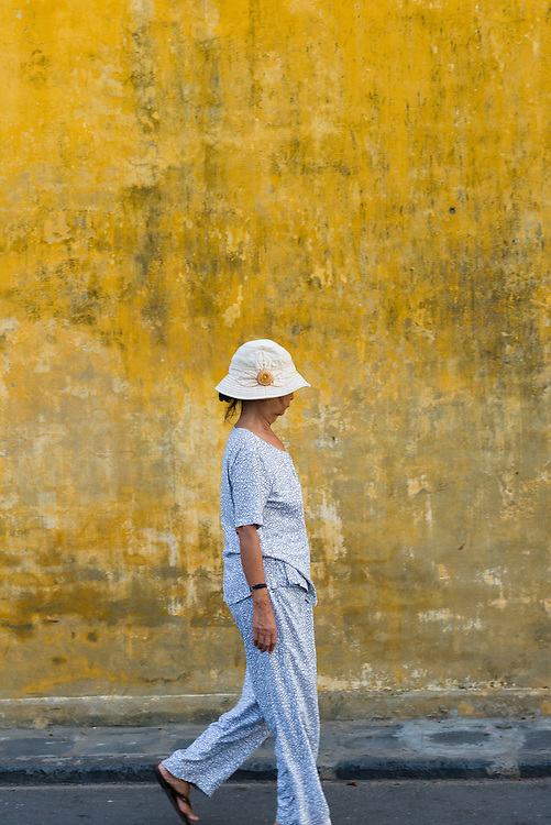Vietnamese woman passing yellow wall of Hoi An Ancient Town