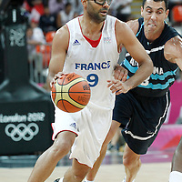 31 July 2012: Tony Parker of France drives past Argentina Pablo Prigioni during 71-64 Team France victory over Team Argentina, during the men's basketball preliminary, at the Basketball Arena, in London, Great Britain.
