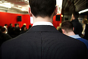 Young man's striped suit at a graduate expo fair where company job recruiters meet young people starting work