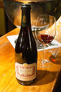 Bottle and glass on a wooden bar counter of Rutini Pinot Noir 1999, Bodega La Rural, Maipu, Mendoza The Rosa Negra Restaurant, The Black Rose, Buenos Aires Argentina, South America San Felipe, La Rural Vinedos y Bodegas Winery