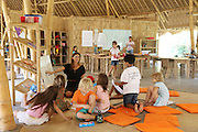 """Primary school class involving participation, enactment and storytelling even whilst doing academic subjects like mathematics and english<br /><br />The Green School (Bali) is one of a kind in Indonesia. It is a private, kindergarten to secondary International school located along the Ayung River near Ubud, Bali, Indonesia. The school buildings are of ecologically-sustainable design made primarily of bamboo, also using local grass and mud walls. There are over 600 students coming from over 40 countries with a percentage of scholarships for local Indonesian students.<br /><br />The impressive three-domed """"Heart of School Building"""" is 60 metres long and uses 2500 bamboo poles. The school also utilizes renewable building materials for some of its other needs, and almost everything, even the desks, chairs, some of the clothes and football goal posts are made of bamboo.<br /><br />The educational focus is on ecological sustainability. Subjects taught include English, mathematics and science, including ecology, the environment and sustainability, as well as the creative arts, global perspectives and environmental management. This educational establishment is unlike other international schools in Indonesia. <br /><br />Renewable energy sources, including solar power and hydroelectric vortex, provide over 50% of the energy needs of the school. The school has an organic permaculture system and prepares students to become stewards of the environment. <br /><br />The school was founded by John and Cynthia Hardy in 2008."""