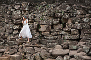 A woman, dressed in a white bridal dress, takes a photo whilst balancing on the ancient stone wall of Angkor Thom, Siem Reap Province, Cambodia, South East Asia.