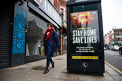 © Licensed to London News Pictures. 15/01/2021. London, UK. A woman wearing walks past the Government's ''Stay Home, Save Lives' Covid-19 publicity campaign poster in north London as research shows that the capital's R rate is below 1. The research from Cambridge University suggests that the rate of transmission might be slowing down in London and the South East, where the mutant variant of the SARS-Cov-2 virus first began spreading. Photo credit: Dinendra Haria/LNP