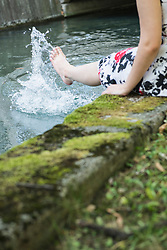 Woman splashing water with her leg at Eisbach Riverbank