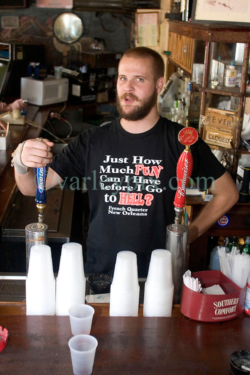 """03 Sept  2005. New Orleans, Louisiana. Post hurricane Katrina.<br /> Johnny White's Sports Bar on Bourbon Street in the French Quarter - with it's claim to """"Never Close."""" The bar has remained open throughout.  Barman Jo Bellomy at the helm.<br /> Photo Credit ©: Charlie Varley/varleypix.com"""