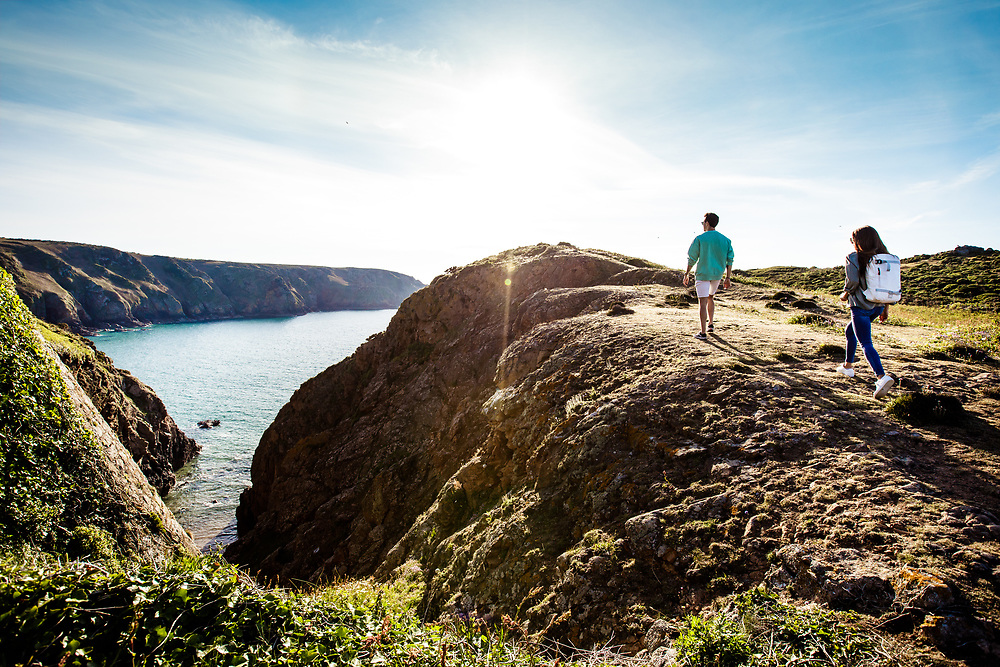 Couple walking and exploring the cliffs and headland at Plemont beach at high tide on a calm, sunny day in Jersey, Channel Islands