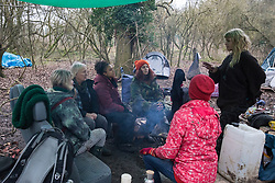 Harefield, UK. 13 January, 2020. Stop HS2 activists sit around a camp fire in a protection camp close to Harvil Road. Part of the nearby Colne Valley protection camp was evicted by bailiffs last week. 108 ancient woodlands are set to be destroyed by the high-speed rail link and further destruction of trees for HS2 in the Harvil Road area is believed to be imminent.