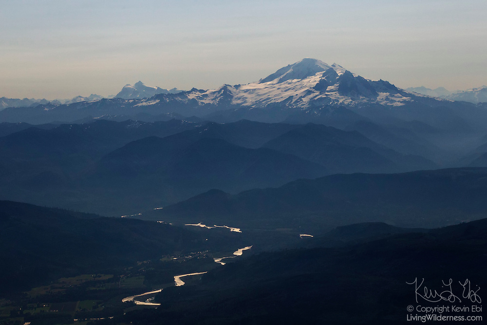 The Skagit River flows away from Mount Baker, a 10781 foot (3286 meter) volcano in the North Cascades of Washington state. Mount Shuksan, a 9131 foot (2783 meter) peak due east of Mount Baker, is visible in the background on the left side of this aerial view over Skagit County.