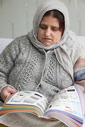 Portrait of South Asian woman reading a catalogue.