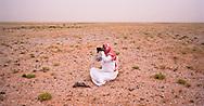 Sheikh Jaber Alamrah keeping an eye on his herd of camels in the Dahana Sands, Saudi Arabia