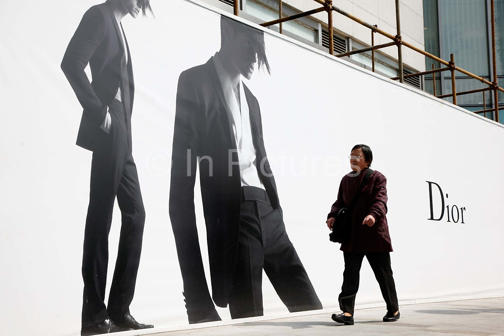 A woman walks past a large luxury goods advert in Shanghai, China on 24 March, 2011.  Some local governments in China are instituting limits or banning outdoor advertisements for luxury brands, in hopes of curbing increasing public awareness of the widening wealth gap.