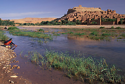 Africa, Morocco, Ait Benhaddou, Girl filling jugs in Oued (river) Ounila and Ksour (village) of Ait Benhaddou