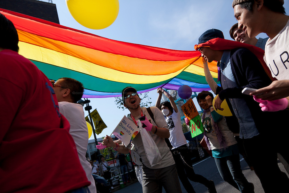 People parade under  a large rainbow flag at Tokyo Rainbow Pride festival, Yoyogi Park, Tokyo, Japan. Sunday April 27th 2014 This was the third year this annual gay-pride event has been held in Japan capital.with food, fashion and health care stalls and musical performances set up in Yoyogi Park event square and a colourful parade around Shibuya at 1pm.