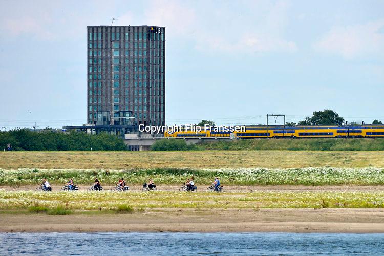 Nederland, Nijmegen, 5-7-2016Zicht op de  nevengeul van de Waal bij Lent en het lentereiland .  Het dorp veurlent ligt nu op een kunstmatig eiland met twee kleinere bruggen als ontsluiting. Een voetgangersbrug, de steltlopersbrug op de foto, voor wandelaars naar het recreatiegebied en een andere, de Promenadebrug, voor normaal verkeer. Ruimte voor de rivier, water, waal. Fietsers maken een tochtje over het nieuwe eiland . In de achtergrond vetrekt een trein van station Nijmegen-Lent waarbij ook het pas geopende nieuwe hotel van van der Valk ligt .The Netherlands, Nijmegen Measures taken by Nijmegen to give the river Waal, Rhine, more space to flow during highwater and to prevent the risk of flooding. Room for the river. Reducing the level, waterlevel. Large project to create a new paralel gully, an extra flow of water, so the river can drain more water during highwater. Due to climate change and expected rise, increase of the sealevel, the Dutch continue to protect their land from the water. Foto: Flip Franssen/HH