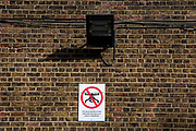 """Warning sign stating """"the use of drones in and over HMP Pentonville is strictly prohibited"""" displayed under a flood light on an external brick wall in HMP Pentonville, London, UK.  HM Prison Pentonville is an English Category B men's prison, operated by Her Majesty's Prison Service. Pentonville Prison is located on  Caledonian Road in the Barnsbury area of the London Borough of Islington, north London, United Kingdom. (Photo by Andy Aitchison)"""