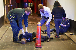 © licensed to London News Pictures. London, UK 14/12/2013. Emergency services helping a drunk man in Soho, London on the last Friday night before Christmas, which is also the busiest night of the year for emergency services. Photo credit: Tolga Akmen/LNP