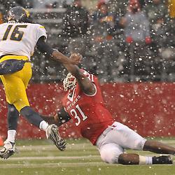 Dec 5, 2009; Piscataway, NJ, USA; West Virginia quarterback Jarrett Brown (16) straight-arms Rutgers defensive end George Johnson (31) to seal his team's victory during second half NCAA Big East college football action in West Virginia's 24-21 victory over Rutgers at Rutgers Stadium.