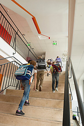 Rear view of school students walking up on stairs, Munich, Bavaria, Germany
