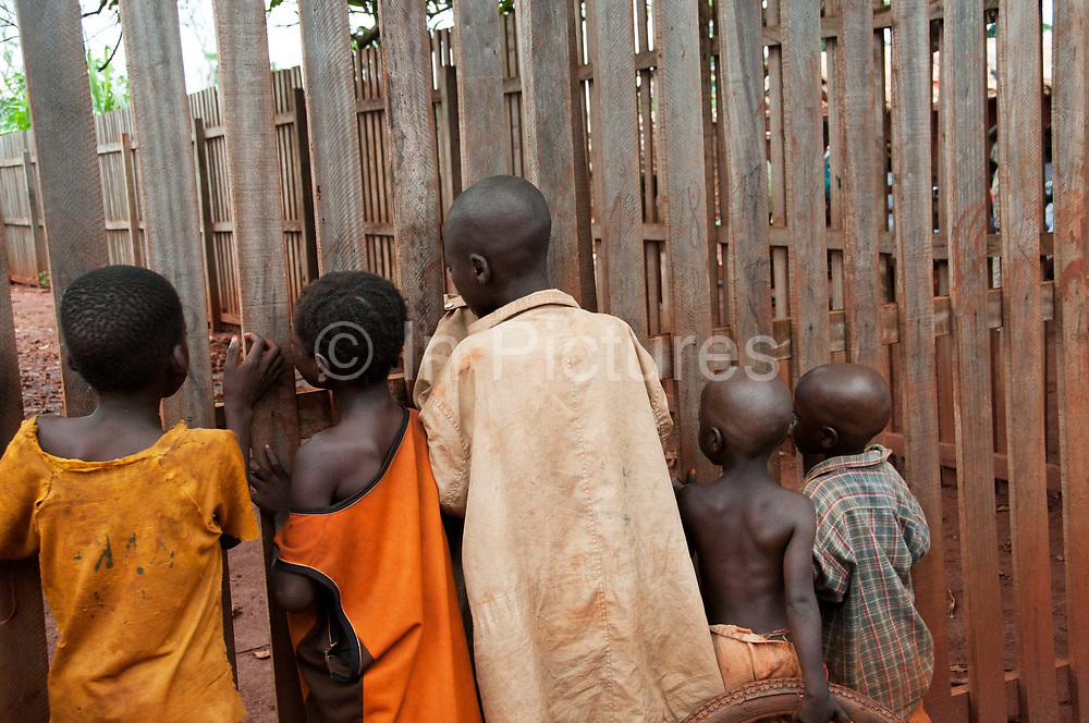 Central African Republic. August 2012. Batalimo camp for refugees from the Democratic Republic of Congo. Young boys listening to a film being shown in a hut on the other side of the fence.