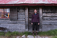 An Alaskan Woman stands in front of the door of Fure's Cabin on the North Arm of Naknek Lake, Alaska