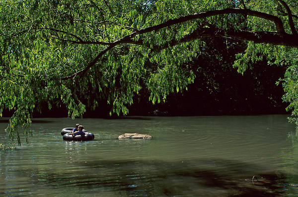 Stock photo of children tubing in the river on a hot afternoon