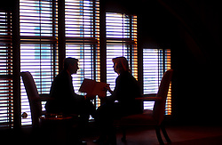 Stock photo of the silhouette of two business associates sitting together in front of a window in an office building