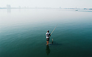 A Vietnamese man fishes in West Lake in Tay Ho, Hanoi, Vietnam, Southeast Asia