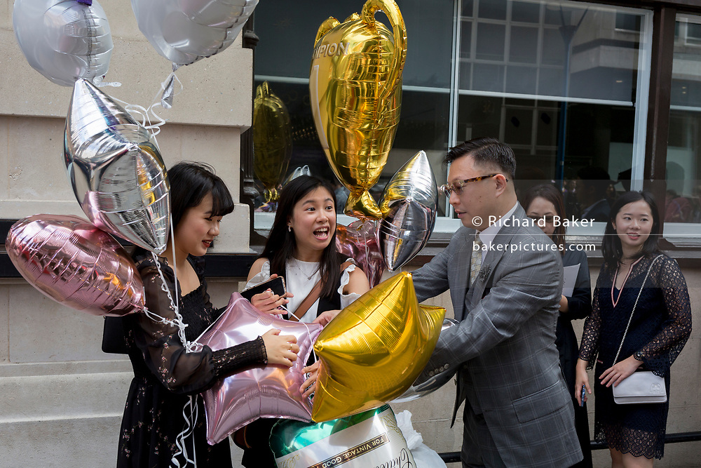 Friends and family of Hillary Chung, a 21 year-old Law graduate from Hong Kong, celebrate her graduation with a 2:1 degree outside the London School of Economics (LSE) after her graduation ceremony, on 22nd July 2019, in London, England.