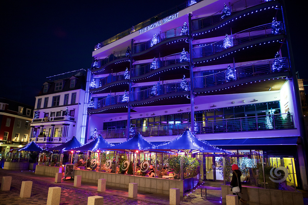 The Royal Yacht outdoor restaurant and hotel lit up with Christmas decorations at night in St Helier, Jersey