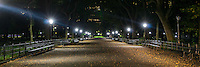 Late night in Central Park as the street lights illuminate the path through the park.