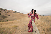 Lifestyle portrait of a yoga teacher and writer sitting on a fence wearing a red dress and a hat in the foothills of Boulder, CO.