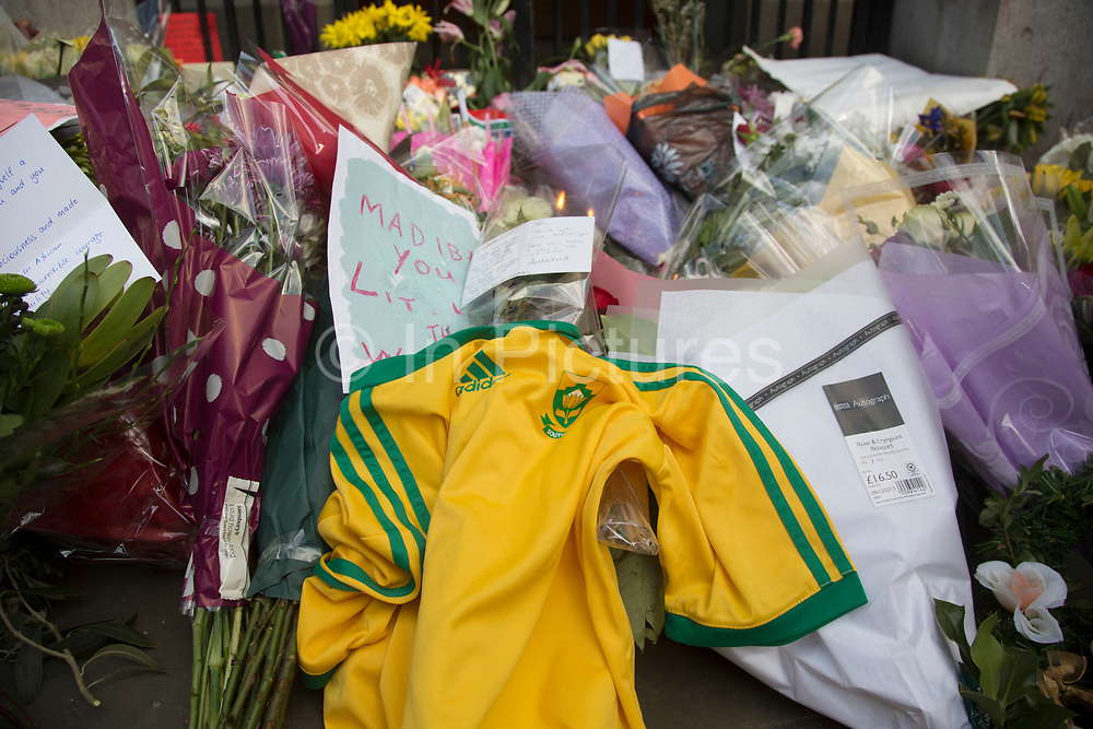 London, UK 6th December 2013: Floral tributes near to the South African Embassy to pay tribute to former South African leader and anti-apartheid ANC campaigner Nelson Mandela, who died aged 95 on 5th December 2013.