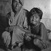 Noorbanu and her daughter in their hovel at Mirpur. Their only possessions are a few mud pots and a rusted tin full of flour from the relief lines.  Each night they must pish and shove anew to maintain their sleeping space amongst the scores of others around them.  Bangladesh, 1977