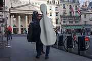 Two cellists chat in the street, opposite the Theatre Royal Harmarket, on 29th September 2016, in central London, England. With their instruments strapped to their backs, the two musicians talk, perhaps before starting a nights work at a nearby theatre im the capitals West End, the location for many stage and musical productions such as Phantom of the Opera.