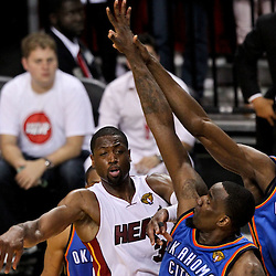 Jun 21, 2012; Miami, FL, USA; Miami Heat shooting guard Dwyane Wade (3) passes the ball off as Oklahoma City Thunder center Kendrick Perkins (5) and power forward Serge Ibaka (9) defend during the second quarter in game five in the 2012 NBA Finals at the American Airlines Arena. Mandatory Credit: Derick E. Hingle-US PRESSWIRE