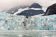 The Surprise glacier with the medial moraine running down the middle and brash ice floating in Surprise Inlet, Harriman Fjord, near Whittier, Alaska. Surprise Glacier is the most active calving tidewater glacier in Prince William Sound.